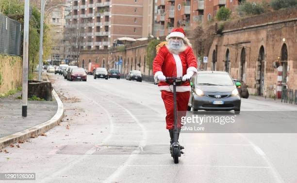 Man dressed as Santa Claus rides an electric scooter around Rome on December 08, 2020 in Rome, Italy. While decorations go up to celebrate the...