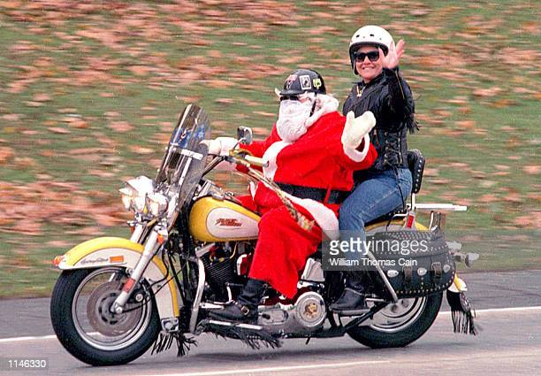 A man dressed as Santa Claus rides his Harley Davidson with a friend on Rt 263 in Warminster Pa on their way to deliver toys to children in...