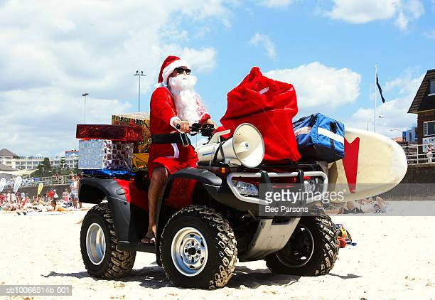 Man dressed as Santa Claus riding on quadbike on beach