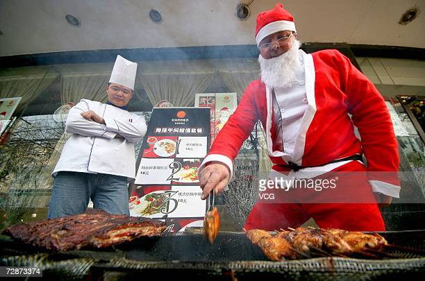 A man dressed as Santa Claus roasts beef on December 23 2006 in Nanjing Jiangsu Province China While Christmas Day is not a public holiday Christmas...