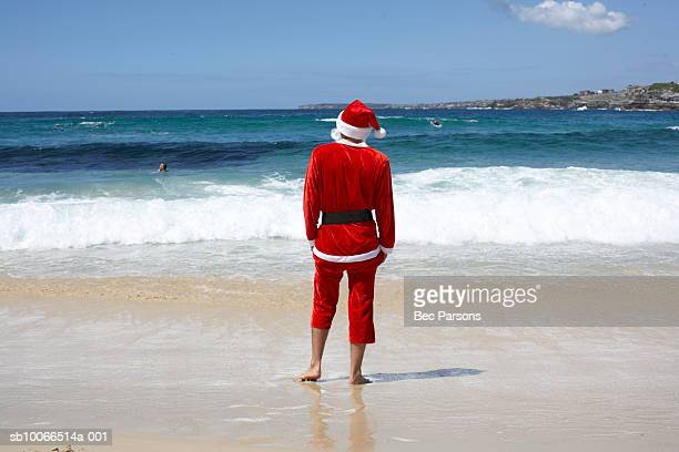 Man dressed as Santa Claus standing on beach, looking at sea, rear view