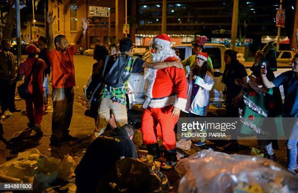 A man dressed as Santa Claus talks to homeless during the event 'Santa en las calles' in the streets of Caracas on December 16 2017 'Santa in the...