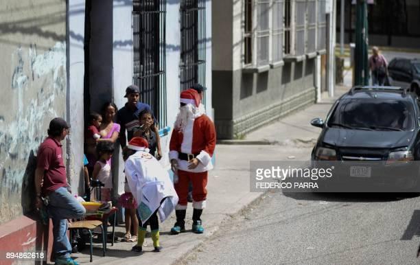 A man dressed as Santa Claus talks to people during the 'Santa en las calles ' event in the Pastora shantytown in Caracas on December 16 2017 Santa...