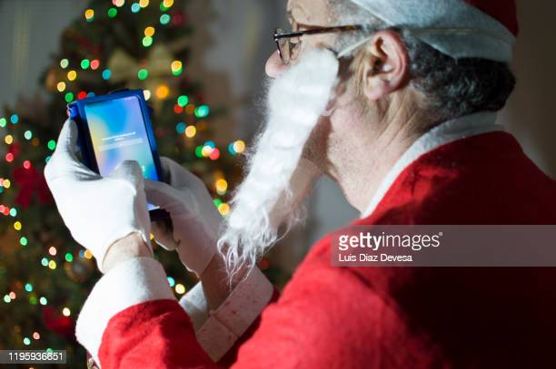 man dressed as santa claus using smart phone in front of christmas tree - 2020 2029 stock pictures, royalty-free photos & images