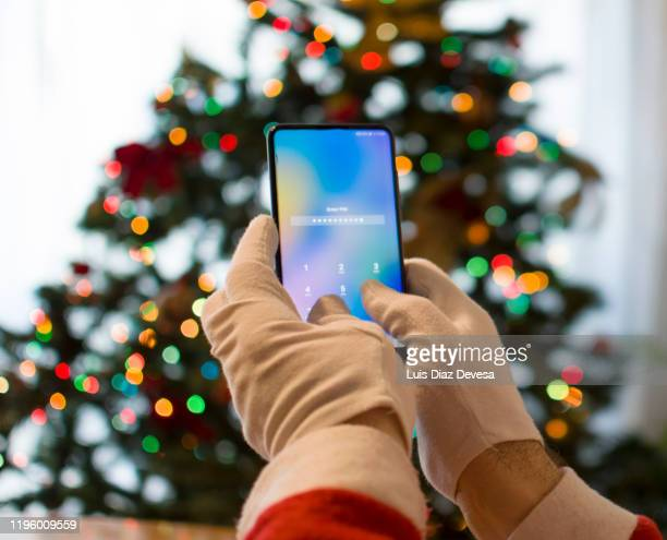 man dressed as santa claus using smart phone in front of christmas tree - この撮影のクリップをもっと見る 2025 stock pictures, royalty-free photos & images