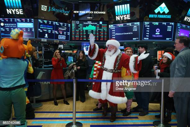 A man dressed as Santa Claus visits the floor of the New York Stock Exchange ahead of the closing bell November 30 2017 in New York City On Thursday...