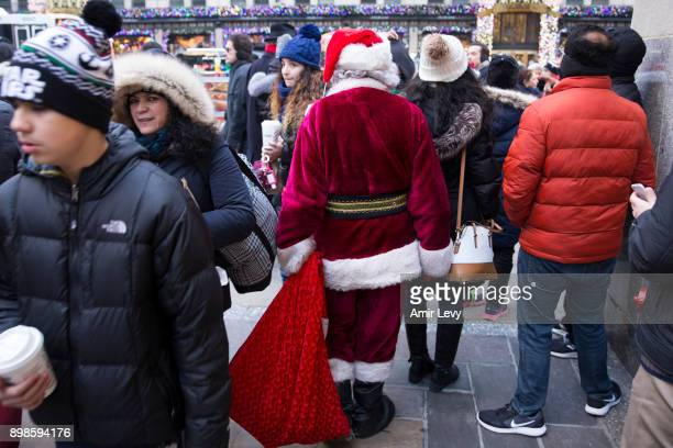 A man dressed as Santa Claus walk along Fifth Avenue on Christmas day on December 25 2017 in New York City Security in New York is on alert as...