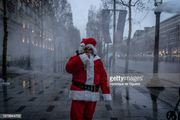 A man dressed as Santa Claus walks along the street after the Yellow Vests march December 15 2018 in Paris France The protesters gathered in Paris...