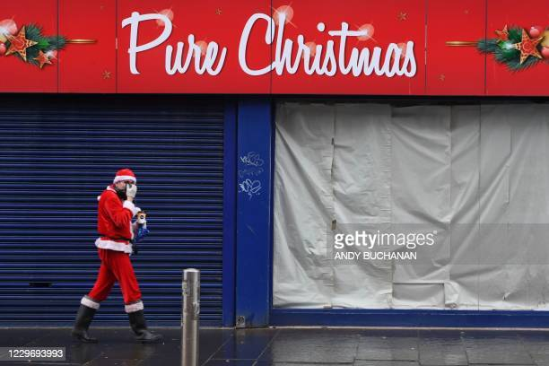 Man dressed as Santa Claus walks past a closed Christmas shop in central Glasgow ahead of the introduction of further coronavirus restrictions on...