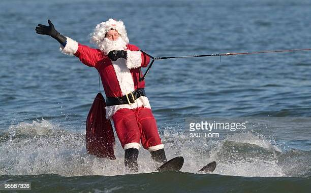 A man dressed as Santa Claus water skis on the Potomac River at the National Harbor in Prince George's County Maryland near Washington DC on December...
