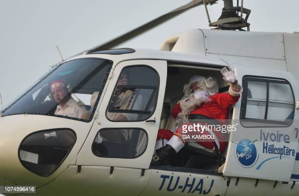 A man dressed as Santa Claus wave from a helicopter as he arrives at the presidential palace in Abidjan on December 22 during a Christmas event...