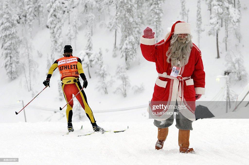 A man dressed as Santa Claus waves as he : News Photo