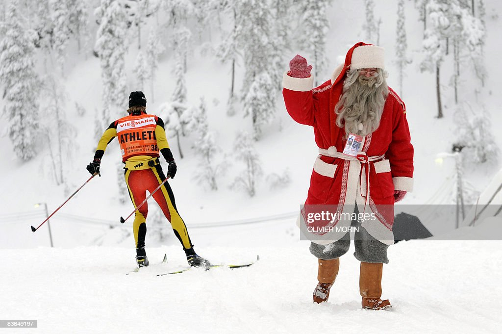 A man dressed as Santa Claus waves as he arrives at the nordic skiing arena as an athlete skis past before the World Cup ski jumping team HS 142 event on November 28, 2008, in Kuusamo-Ruka.