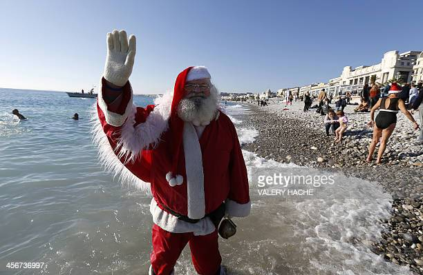 A man dressed as Santa Claus waves on December 15 2013 on the beach in Nice as part of a traditional christmas winter sea swimming event AFP PHOTO /...