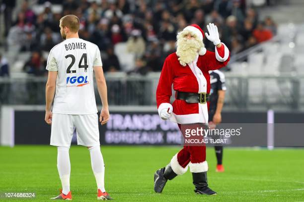 TOPSHOT A man dressed as Santa Claus waves on the pitch prior to the French L1 football match between Bordeaux and Amiens on December 23 2018 at the...
