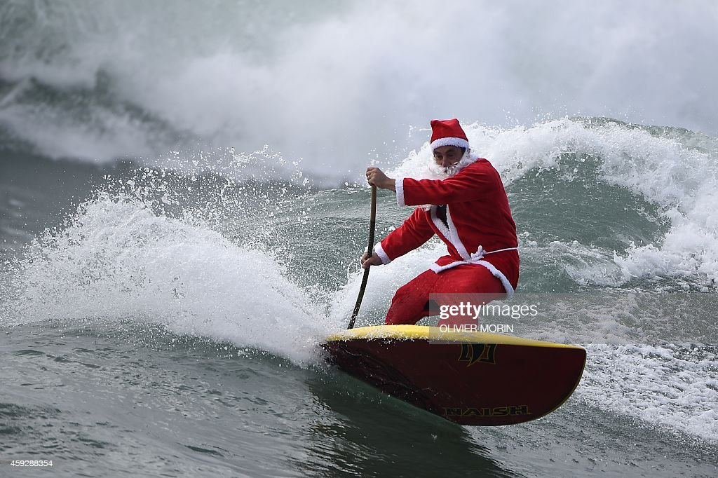 A man dressed as Santa Klaus rides a wave with a stand up paddle (SUP) on November 18, 2014 in Varazze, near Genoa, as the bad weather created good surfing conditions in Mediterranea.