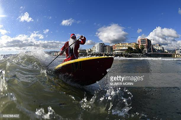 A man dressed as Santa Klaus rides a wave with a stand up paddle on November 18 2014 in Varazze near Genoa as the bad weather created good surfing...