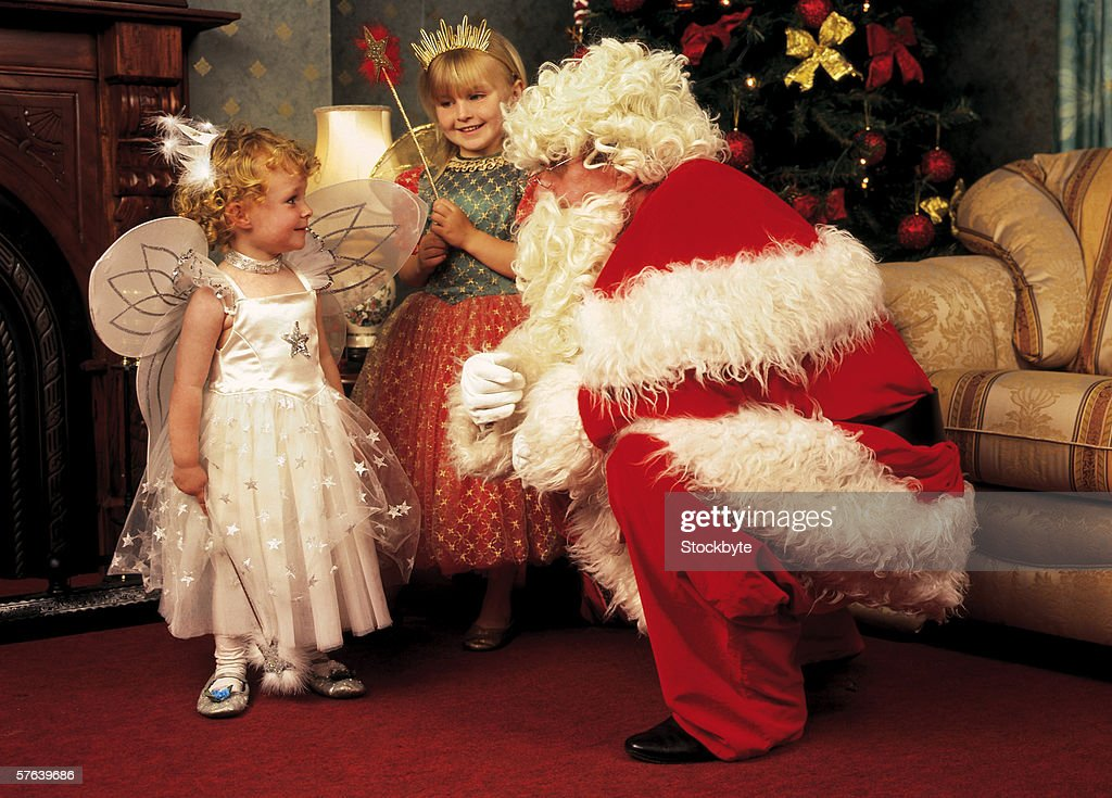man dressed as Santa talking to two little girls in fairy outfits : Stock-Foto