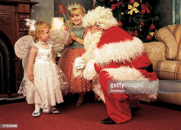 man dressed as Santa talking to two little girls in fairy outfits