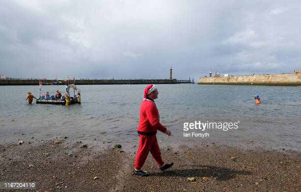 A man dressed as Santa walks along the sand during the raft race at the annual Whitby Regatta on August 10 2019 in Whitby England At over 170 years...