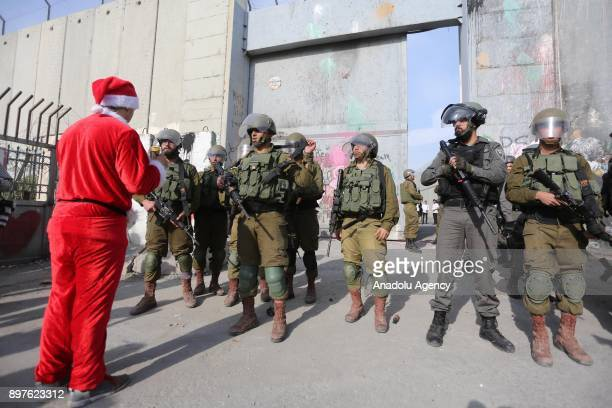 A man dressed as SantaClaus talks with an Israeli security force member as they attend a protest against US President Donald Trumps announcement to...