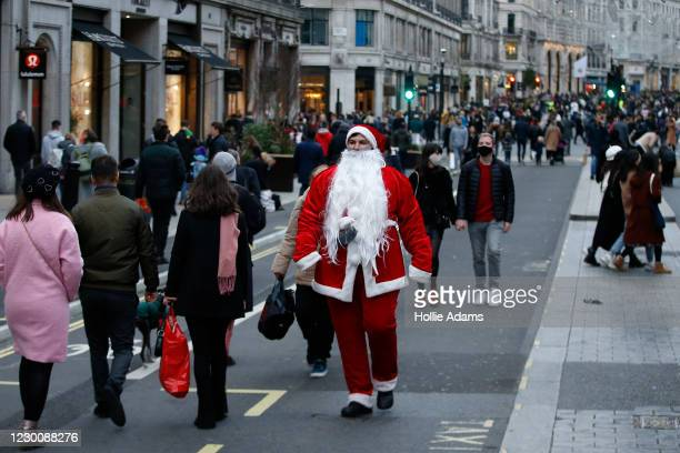 Man dressed as Santas Claus walks amongst Christmas shoppers on Regent Street on December 12, 2020 in London, England.