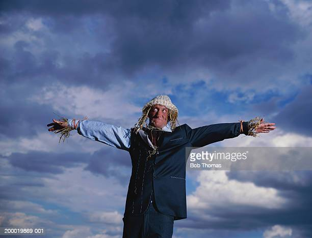 Man dressed as scarecrow standing under cloudy sky
