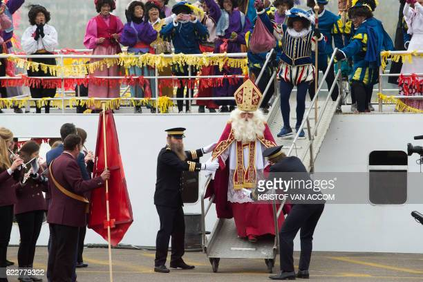 A man dressed as Sinterklaas a is welcomed as he arrives followed a man dressed Zwarte Piet and other participants disguised during on November 12...