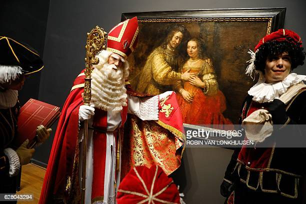 A man dressed as Sinterklaas and another in Zwarte Piet stand on December 6 2016 in front of the 'Joodse Bruidje' Dutch painter Rembrandt during...