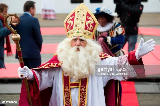A man dressed as Sinterklaas follwoed by another one dressed as Zwarte Piet gestures as he arrives on November 12 2016 in Antwerp Black Pete is the...
