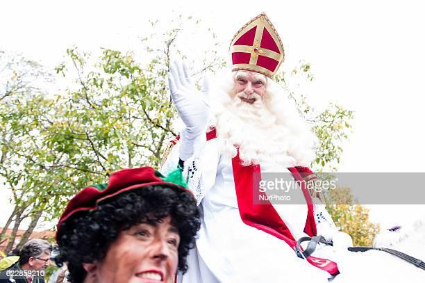 A man dressed as Sinterklaas gestures as he arrives on a horse in Maassluis on November 12 2016 Black Pete is the companion of Saint Nicolas during...