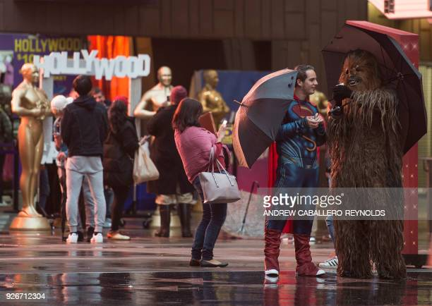 A man dressed as Superman and another as Chewbacca take cover from the rain as they wait to pose with tourists near the red carpet area as...