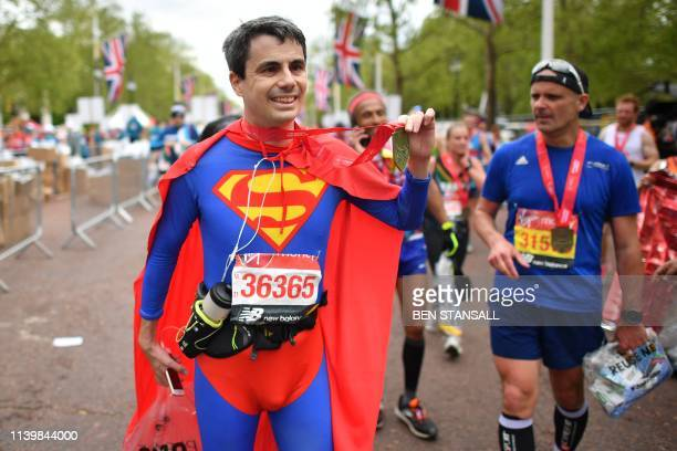 TOPSHOT A man dressed as Superman recovers after running the 2019 London Marathon in central London on April 28 2019 / Restricted to editorial use...