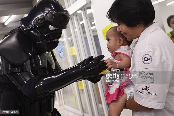 A man dressed as the character Dark Trooper from a famous movie Star Wars plays with a kid during the Star Wars day in Bangkok Thailand on May 4 2016
