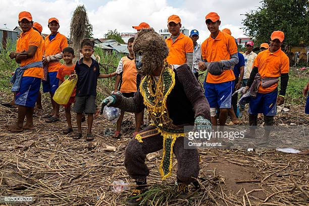 A man dressed as the Hanuman god entertains boat crew members on the morning of the first day of the Water Festival on November 13 2016 in Phnom Penh...