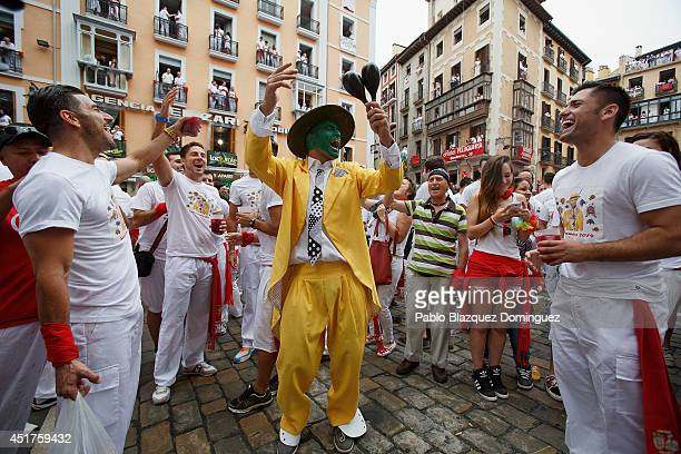 A man dressed as 'The Mask' celebrates with thousands of revellers singing and dancing during the opening and the firing of the 'Chupinazo' rocket...