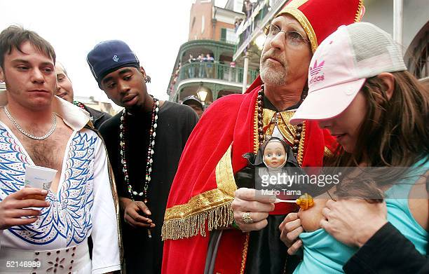 A man dressed as the Pope blesses a woman as revelers including an Elvis impersonator looks on during Mardi Gras festivites February 6 2005 in New...