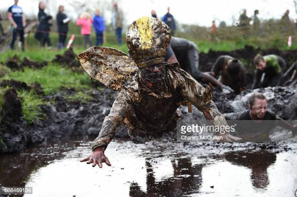 Man dressed as the Pope jumps into a pool of mud as competitors take part in the annual McVities Mud Madness 8km cross country run on April 9, 2017...