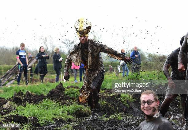 Man dressed as the Pope makes his way around the course as competitors take part in the annual McVities Mud Madness 8km cross country run on April 9,...