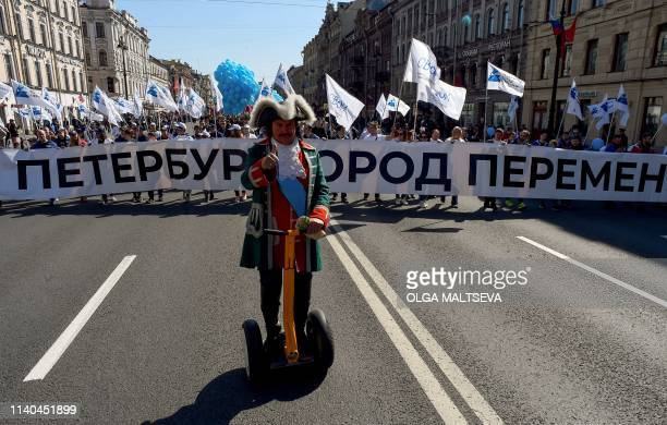 A man dressed as Tsar Peter the Great rides a selfbalancing electronic transportation device in front of demonstrators marching along Nevsky Avenue...