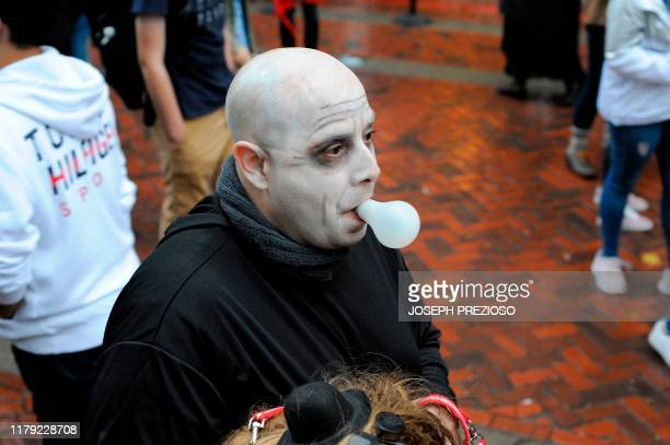 A man dressed as Uncle Fester from the Addams Family walks with a lightbulb in his mouth during Halloween on October 31 2019 in Salem Massachusetts...