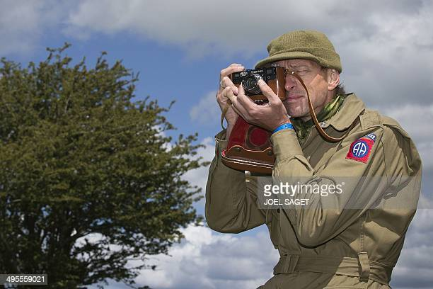 A man dressed as World War II US soldier takes a picture on June 4 2014 in Carentan western France two days before the start of the DDay...