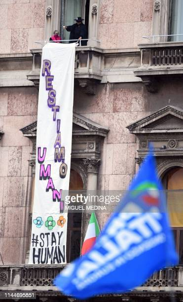 A man dressed as Zorro displays a banner that reads Stay Human from a balcony over Milan's Piazza del Duomo during a meeting of nationalist leaders...