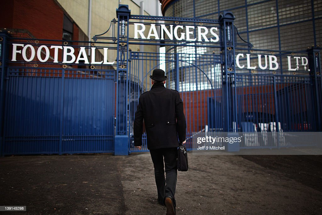 A man dressed in a bowler hat carrying a briefcase walks towards the Ibrox Stadium gates on February 17, 2012 in Glasgow, Scotland. Rangers face Kilmarnock on Saturday following a week where the club went officially into administration, incurring a 10 point penalty from the Scottish Premier League.