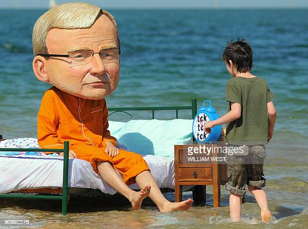 A man dressed in a caricature of Australian Prime Minister Kevin Rudd and pyjamas sits on a bed as a young boy approaches at St Kilda beach in...