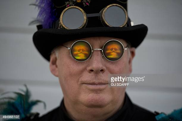 A man dressed in a gothic costume with hologram glasses poses during the biannual Whitby Goth Weekend festival in Whitby northern England on October...