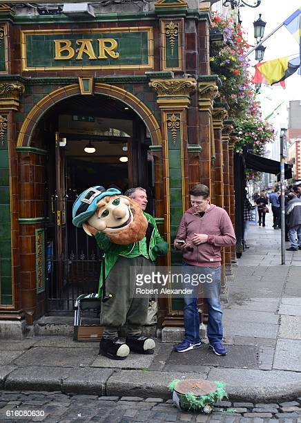 A man dressed in a leprechaun costume hired to attract customers to a Dublin Ireland pub takes a break to talk in front of the pub in Dublin's Temple...