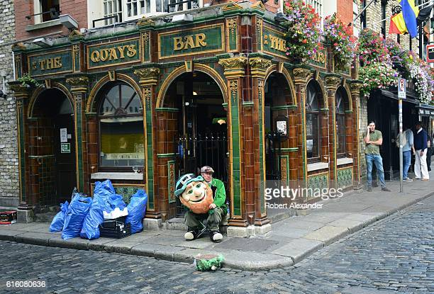 A man dressed in a leprechaun costume hired to attract customers to a Dublin Ireland pub takes a break in front of the pub in Dublin's Temple Bar...