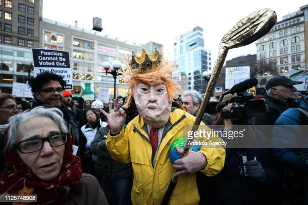 A man dressed in a mask as depicts US President Donald Trump hold golf bat during a President's Day protest against US President Trump and his...