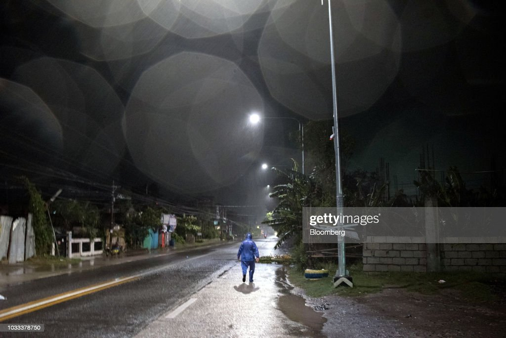 A man dressed in a raincoat walks on an empty street ahead of Typhoon Mangkhut's arrival in Tuguegarao, Cagayan province, the Philippines, on Friday, Sept. 14, 2018. Super Typhoon Mangkhut is expected to threaten Chinas Guangdong coastline, and Hong Kong, with a possible direct strike that may cause as much as $120 billion in damage and economic losses. Photographer: Carlo Gabuco/Bloomberg via Getty Images